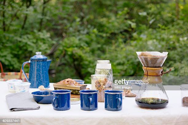 Table in a garden, with a coffee maker, mugs and bowls, a cake and cereal.