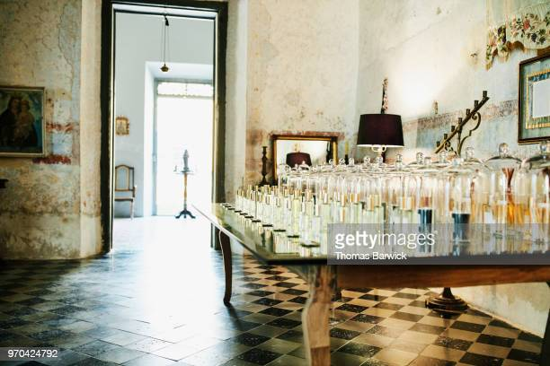 table in perfumery filled with fragrances for customer to sample - perfume stock pictures, royalty-free photos & images