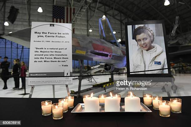A table is set with candles and a picture of actress Carrie Fisher as Princess Leia for a candlelight vigil for the actress at the The Wings Over the...