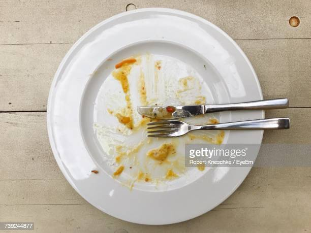 Table Knife And Fork In Empty Plate With Leftover On Table
