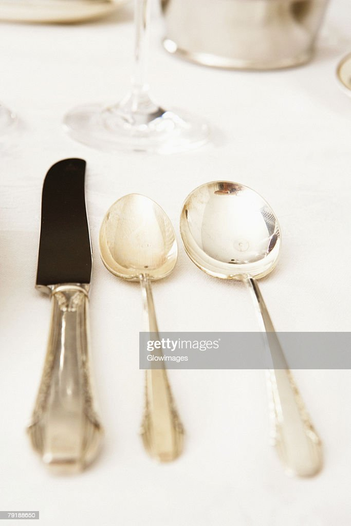 Table knife with two spoons on a dining table : Foto de stock