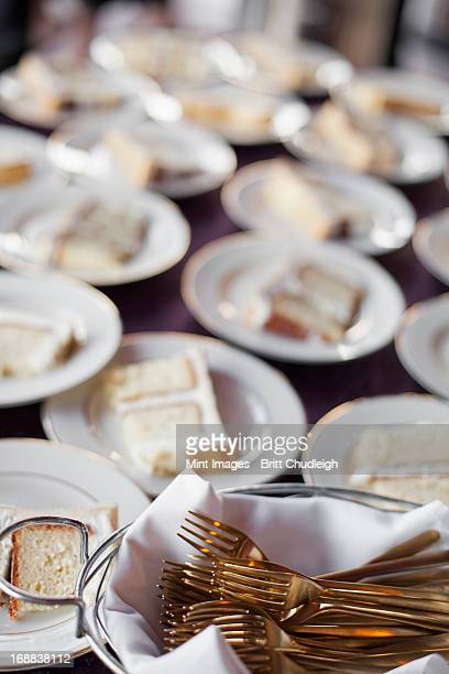 a table laden with plates. white china, and a basket full of dessert forks. a slice of wedding cake.  - utah wedding stock pictures, royalty-free photos & images