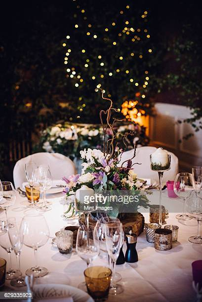A table laid for a special occasion, with a floral centrepiece and candles, at night.