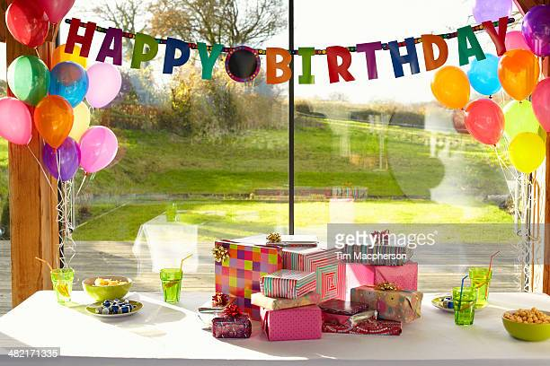 table laid with birthday gifts and balloons - happy birthday stock pictures, royalty-free photos & images