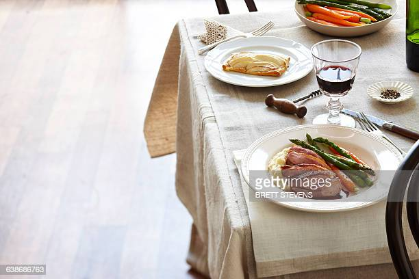 Table meal with plates of duck breast, carrots, asparagus and mashed potato, and apple tart