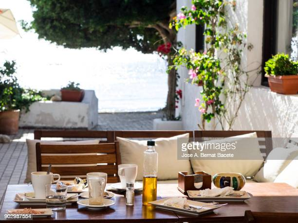 Table of a terrace of bar in the street close to the sea, with the plates and glasses of a breakfast. To the bottom a person walks close to the beach. San Jose, Cabo de Gata - Nijar Natural Park, Beach, Almeria, Andalusia, Spain