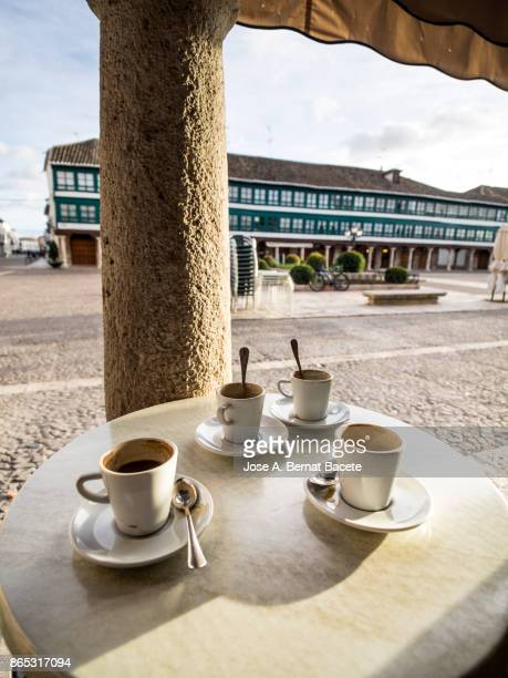 Table of a terrace of bar outdoors with cups of coffee in the ancient square of Almagro, Ciudad Real, Spain.