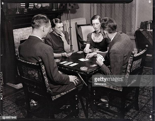 A table of bridge players A man points to cards on the table as his partner puts her hand to her mouth Photograph circa 1950's