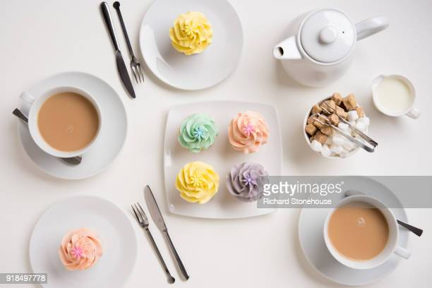 table place setting with english tea and cupcakes