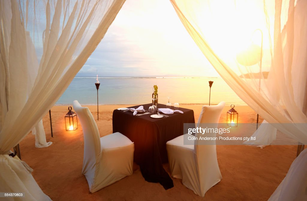 Table prepared for romantic dinner at beach : Stock Photo