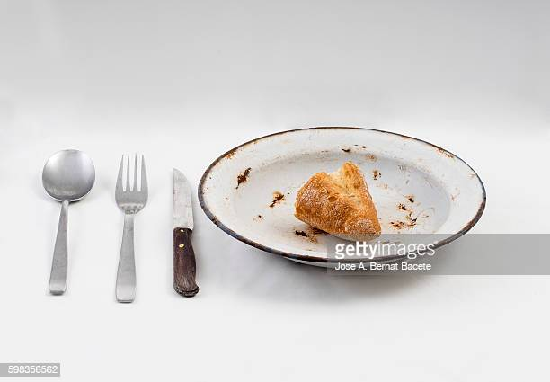 Table prepared with tablecloth, cutlery and metallic plate with a lata of empty conserve