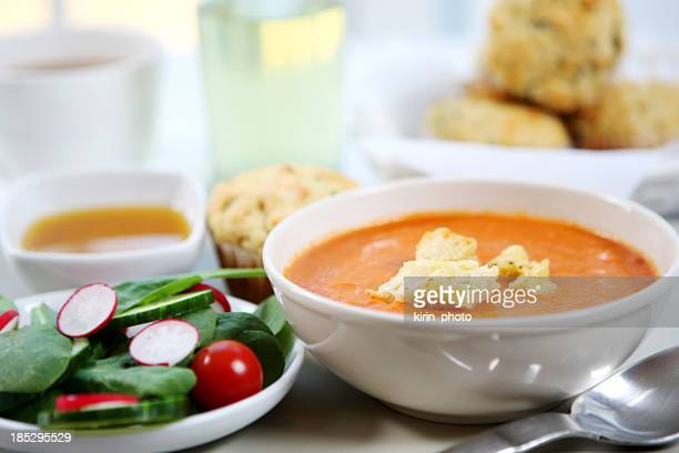 A table served with tomato soup, savory muffins and salad