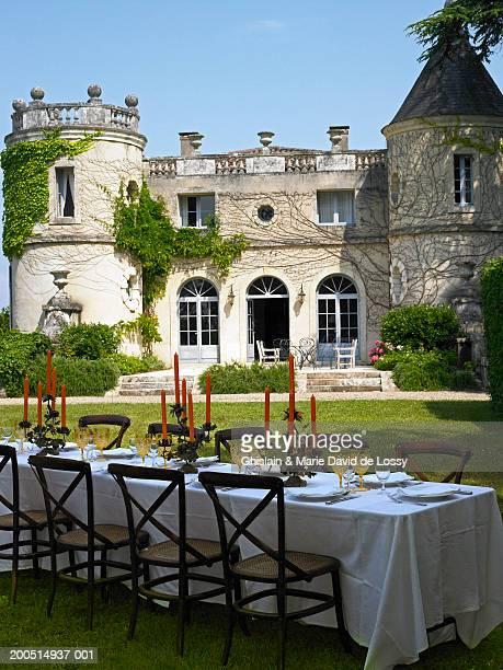 table set for meal on lawn of castle - château photos et images de collection