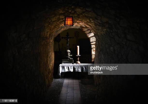 a table set with a candle and skull in a cellar - dungeon stock photos and pictures