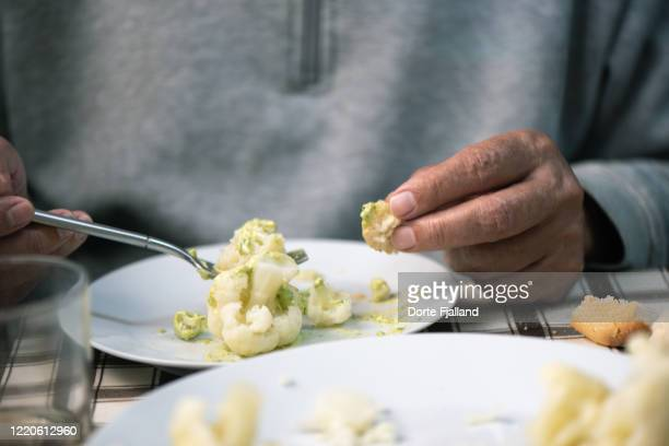 table set with a plate of cauliflower partly eaten by the person whose hands are visible - dorte fjalland imagens e fotografias de stock