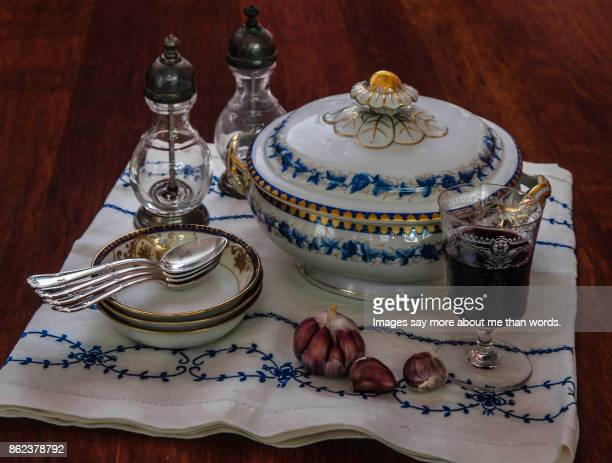 Table set with soup bowl, wine glass, silver spoons, plates and salt shaker. Blue and white tablecloth.