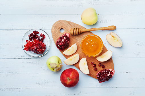 Table set with traditional food for Jewish New Year Holiday, Rosh Hashana. Honey, apple slices and pomegranate. Flat lay. 836241532