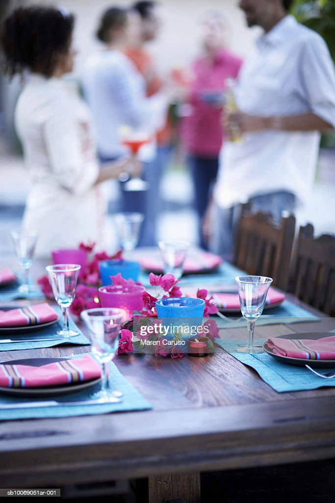Table setting for dinner party, people standing in background : Stockfoto