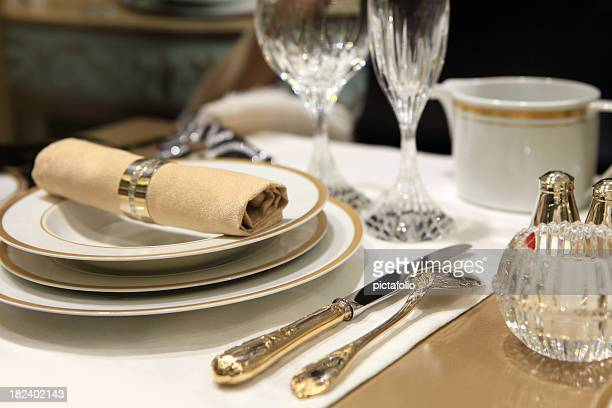 A table setting of fine china and crystal with beige linens
