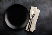 Table setting with empty black plate, fork and knife cutlery and linen napkin on dark table