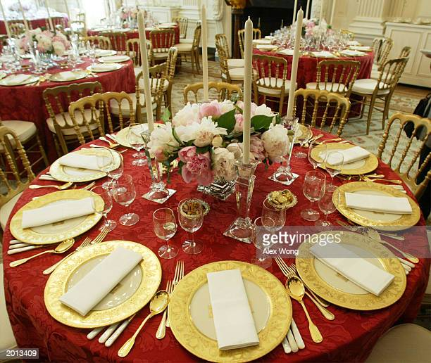 Table settings, prepared for the state dinner for Philippines President Gloria Macapagal Arroyo, adorn a table in the State Dining Room of the White...