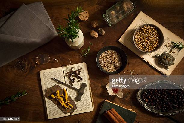 A table spread with a variety of spices and aromatics, coriander, nutmeg, saffron, cloves and rosemary and two old recipe books.