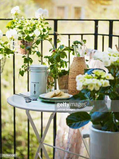Table surrounded by flowers on balcony