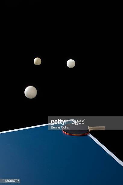 Table tennis balls mid-air and a bat on a table