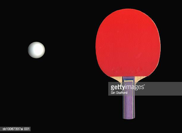Table tennis paddle and ball on black background