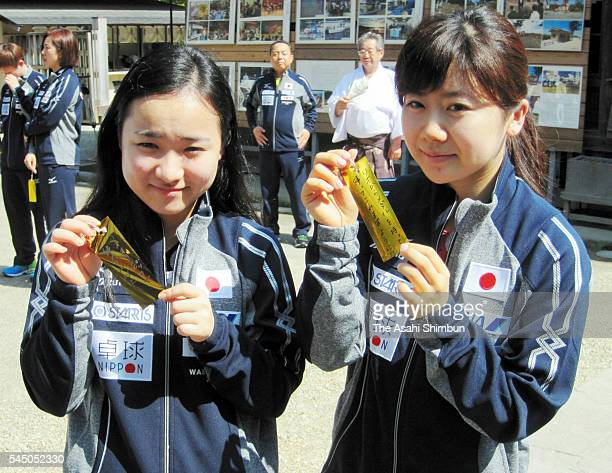 Table tennis players Mima Ito and Ai Fukuhara show strips of paper which they have written their wishes ahead of the Tanabata Festival at Osaki...