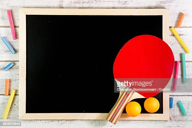 Table Tennis Racket And Balls With Blackboard On Table