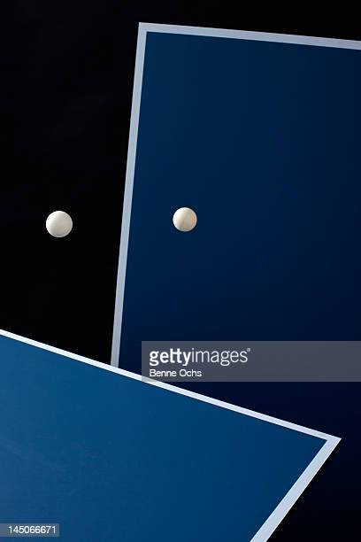 Table tennis tables and balls mid-air
