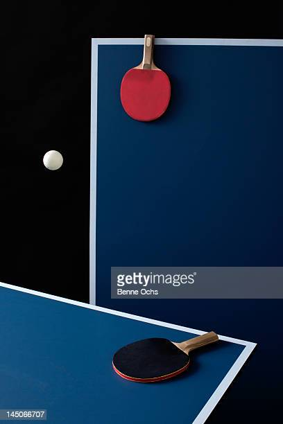 Table tennis tables, bats and a ball mid-air