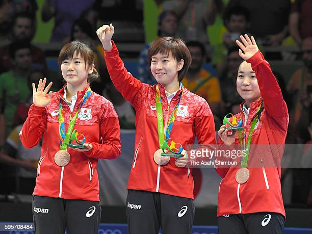 Table tennis Women's Team bronze medalists Ai Fukuhara Kasumi Ishikawa and Mima Ito of Japan pose for photographs on the podium at the medal ceremony...