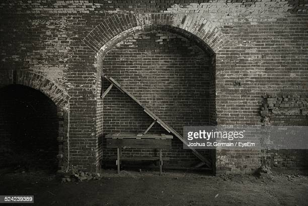 Table Under Arch of Old Brick Wall