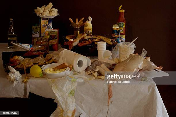 a table with a grill and an excess of various grilling meats and barbecue foods, still life - wine stain stockfoto's en -beelden