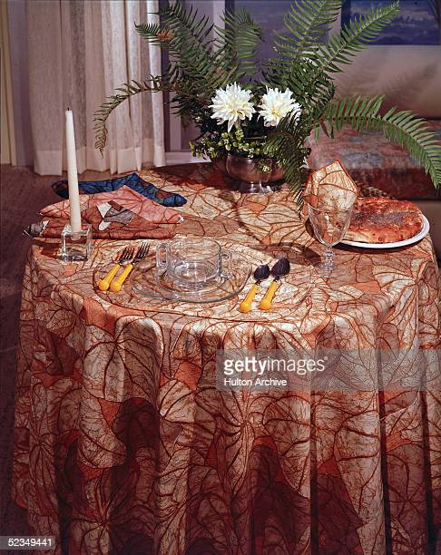 A table with a notable brown patterned tablecloth is shown set for one person with utensils a saucer or plate a bowl or mug a glass napkins a candle...