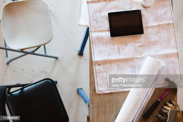 Table with blueprints, notebook and tools