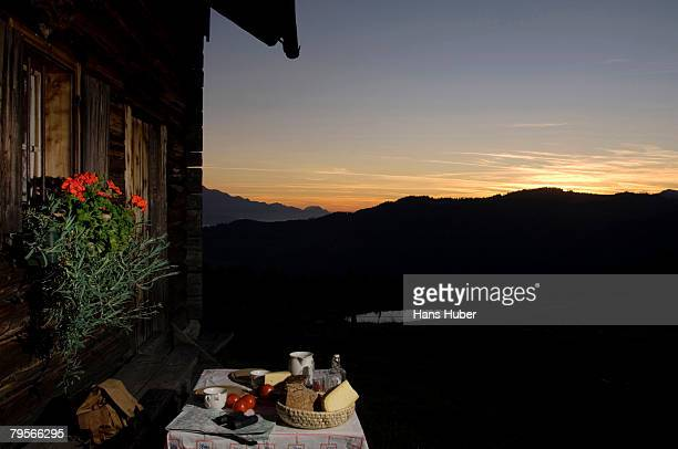 Table with bread and cheese in front of alpine hut