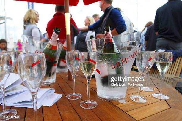 A table with champagne bottles and glasses as the champagne flows at the Champagne Mumm bar in Cowes Yacht Haven on the third day of Cowes Week the...