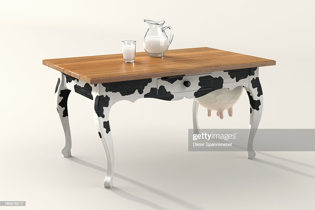 Table with cow print and udder, milk in carafe : Foto de stock
