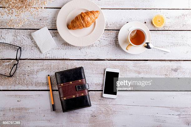 Table with croissant, tea, smart phone and personal organiser