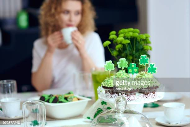 table with cupcakes and woman in background at an irish party. debica, poland - st patricks background stock pictures, royalty-free photos & images
