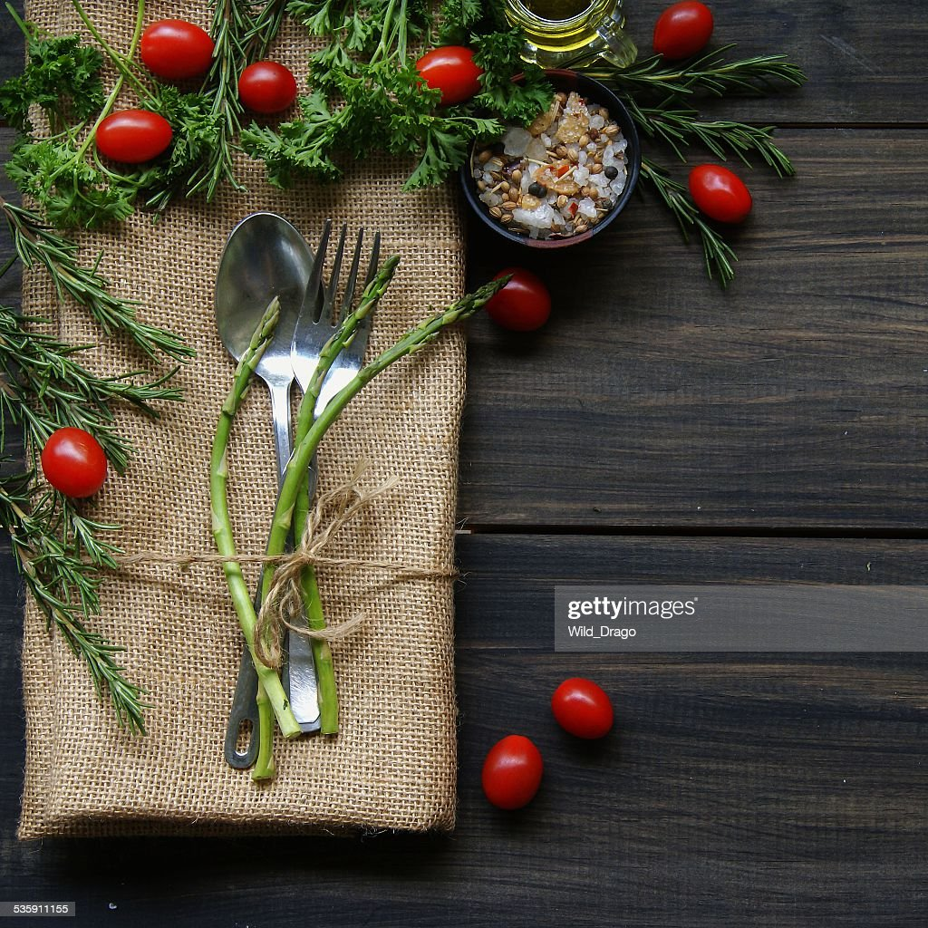 Table with cutlery, herbs, tomatoes and spices : Stock Photo