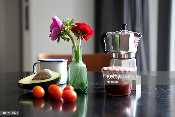 A table with espresso maker, coffee cup and ingredients for breakfast