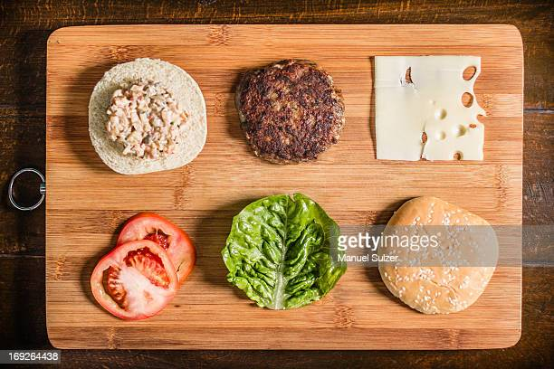 table with hamburger and condiments - hamburger stock pictures, royalty-free photos & images