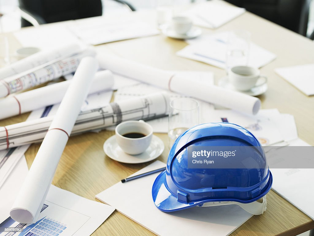 Table with hard-hat and blueprints : Stock Photo