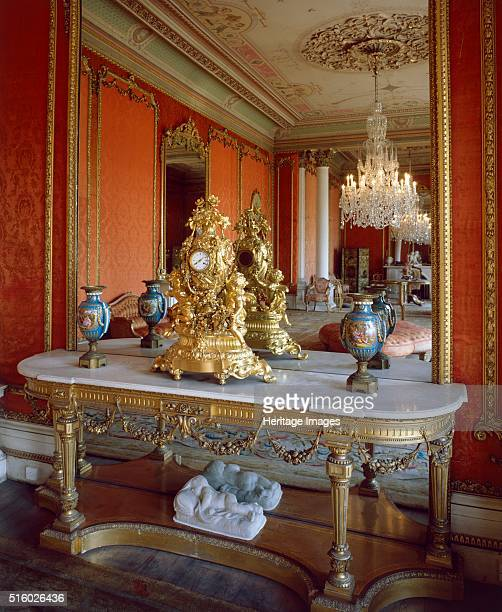 Table with ornate clock in front of a mirror in the drawing room Brodsworth Hall South Yorkshire c2000s Brodsworth was designed for Charles...