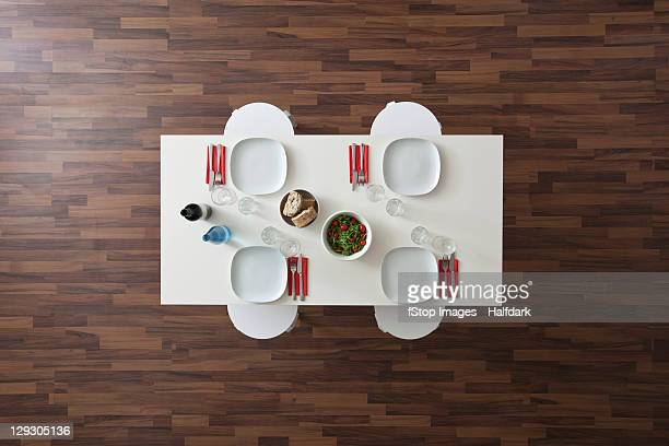 A table with place settings, wine, water, salad and bread, no people, overhead view