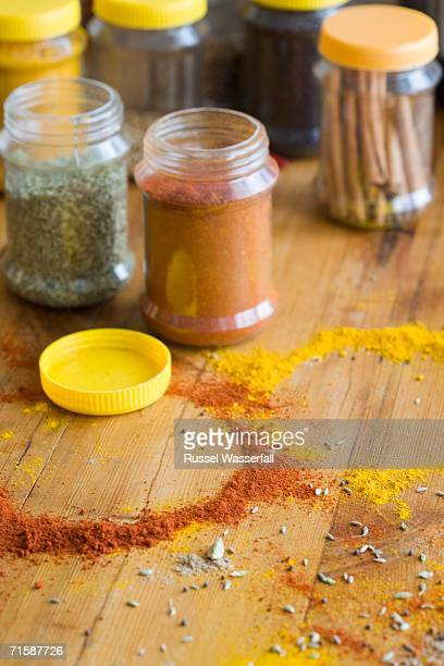 Table with Spice Containers Filled Marsala, Caraway Seeds and Cinnamon Sticks